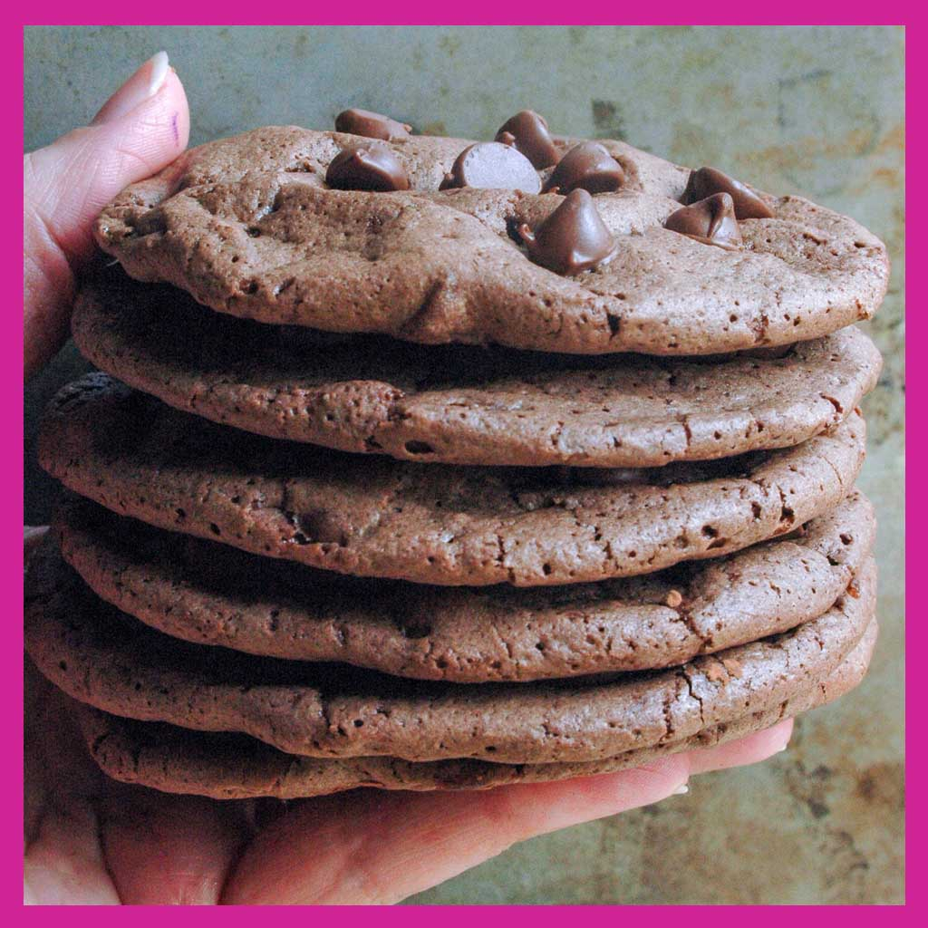 hand holding stack of chocolate chip brownie cookies